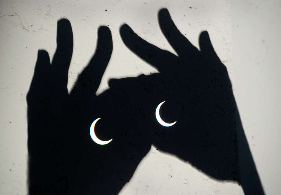 The annular eclipse is visible through binoculars in Sacramento, Calif., Sunday, May 20, 2012. The annular eclipse, in which the moon passes in front of the sun leaving only a golden ring around its edges, was visible to wide areas across China, Japan and elsewhere in the region before moving across the Pacific to be seen in parts of the western United States. (AP Photo/The Sacramento Bee, Randy Pench)  MAGS OUT; TV OUT; MANDATORY CREDIT Photo: AP
