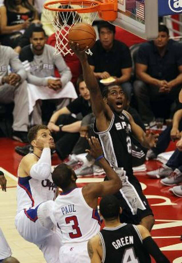 Spurs' Kawhi Leonard (02) goes for a reverse layup against the Los Angeles Clippers' Blake Griffin (32) and Chris Paul (03) in the first half of game four of the Western Conference semifinals at the Staples Center in Los Angeles on Sunday, May 20, 2012. Kin Man Hui/Express-News (Kin Man Hui / SAN ANTONIO EXPRESS-NEWS)