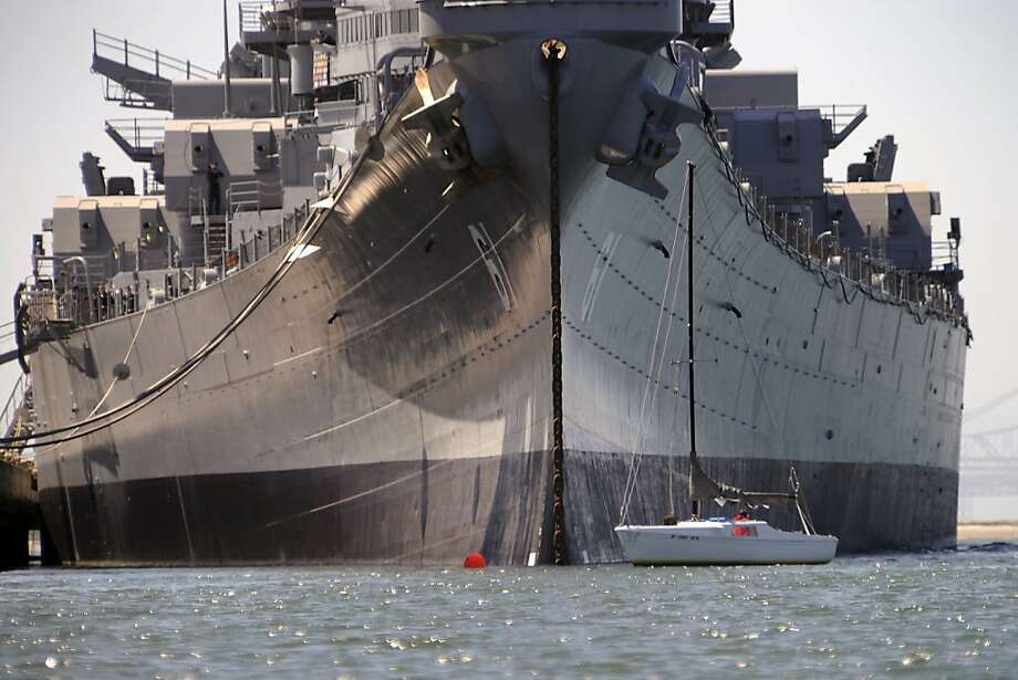 A Sailboat is dwarfed by the USS Iowa battleship as it sits at dock in Richmond, CA Sunday May 20th, 2012.  The Iowa was ready to be towed to Los Angeles today to become a permanent museum but the departure was delayed due to weather issues down the California coast. Photo: Michael Short, Special To The Chronicle