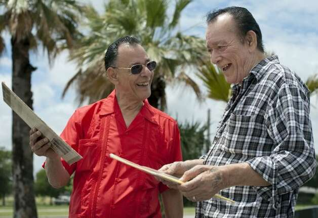Flaco Jimenez (right) and Santiago Jimenez, Jr. look at two of their previous album covers from the 1960s, at Woodlawn Lake on Tuesday, May 15, 2012. (Darren Abate / For the Express-News)