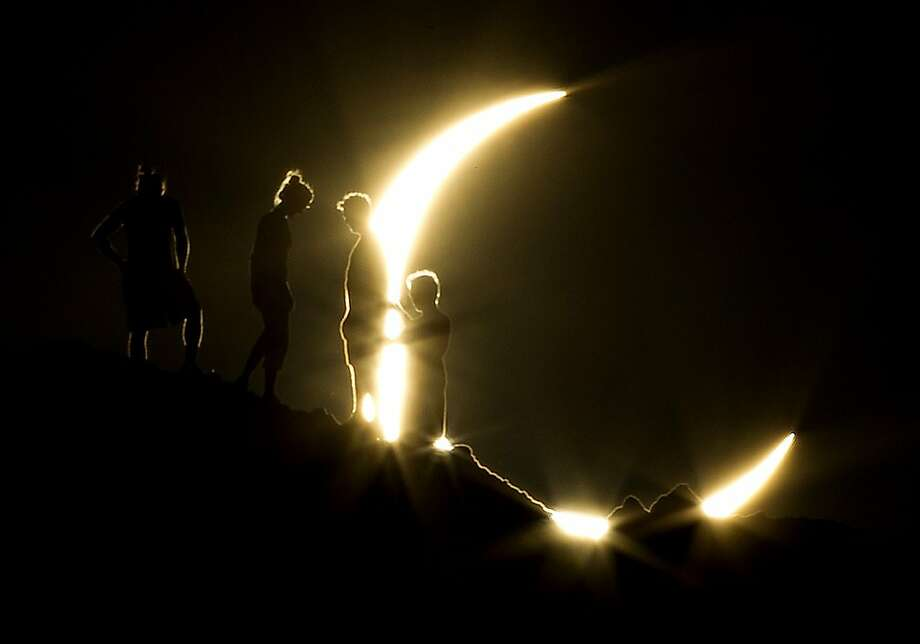 Hikers watch an annular eclipse from Papago Park in Phoenix on Sunday, May 20, 2012. The annular eclipse, in which the moon passes in front of the sun leaving only a golden ring around its edges, was visible to wide areas across China, Japan and elsewhere in the region before moving across the Pacific to be seen in parts of the western United States. (AP Photo/The Arizona Republic, Michael Chow) Photo: Michael Chow, Associated Press