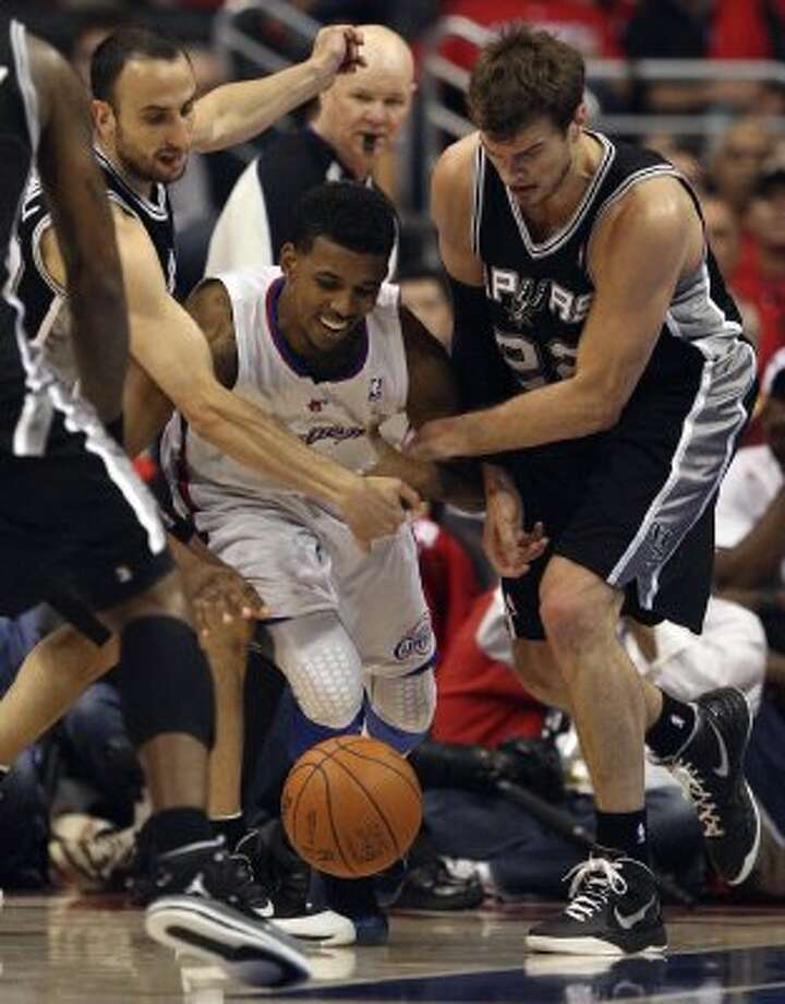 San Antonio Spurs Stephen Jackson (03), Manu Ginobili (20) and Tiago Splitter (22), surround Los Angeles Clippers Nick Young (11), during game four of the Western Conference semifinals at Staples Center in Los Angeles, Sunday, May 20, 2012.  Jerry Lara/San Antonio Express-News (Jerry Lara / San Antonio Express-News)