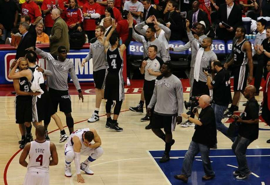The Spurs celebrates as Los Angeles Clippers' Blake Griffin (bottom left) contemplates the loss of game four of the Western Conference semifinals at the Staples Center in Los Angeles on Sunday, May 20, 2012. The Spurs defeated the Clippers, 102-99. Kin Man Hui/Express-News (SAN ANTONIO EXPRESS-NEWS)