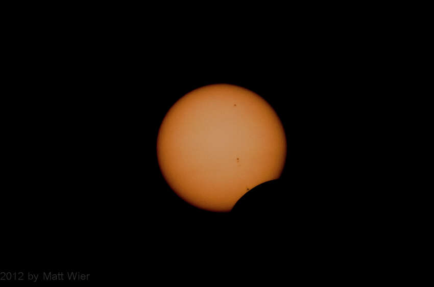 The eclipse begins! Taken with Nikon 200mm with solar filter; sunspots visible. Matt W