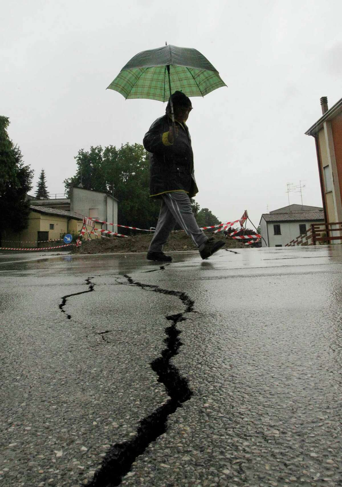 A man walks over a crack that opened in a street in San Carlo, Italy, Monday. A magnitude-6.0 earthquake shook northern Italy early Sunday, killing at least three people and toppling some buildings, emergency services and news reports said. The quake struck at 4:04 a.m. Sunday between Modena and Mantova, about 22 miles)north-northwest of Bologna at a relatively shallow depth of 6 miles, the U.S. Geological Survey said. (AP Photo/Luca Bruno)