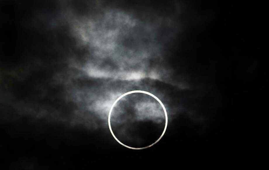 An annular solar eclipse is visible from Machida, on the outskirts of Tokyo, Monday, May 21, 2012. The annular solar eclipse, in which the moon passes in front of the sun leaving only a golden ring around its edges, was visible to wide areas across the continent Monday morning. (AP Photo/Itsuo Inouye) Photo: Itsuo Inouye, STF / AP