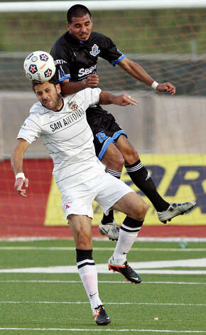 Scorpions' Kevin Harmse and FC Edmonton's Kenny Caceros go up for the ball during first half action Saturday May 19, 2012 at Heroes Stadium. Photo: EDWARD A. ORNELAS, Express-News / © SAN ANTONIO EXPRESS-NEWS (NFS)