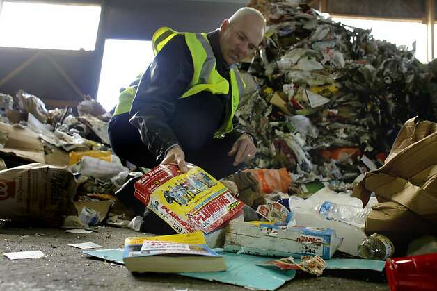 Robert Reed, of the Recology Waste Zero, finds phonebooks in the piles of recycle, Monday January 31, 2011, in San Francisco, Calif. The recycling plant processes 750 tons of glass and paper combined a day. It's unknown how much of that are yellow pages and phonebooks, but it is thought of as an environmental problem. Photo: Lacy Atkins, The Chronicle