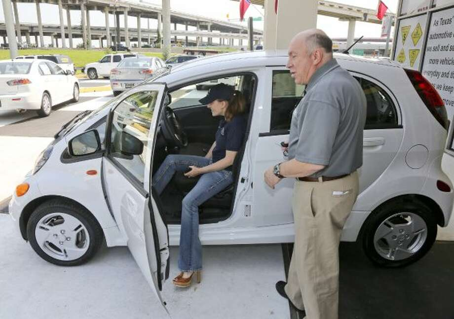 Lee Van Damm of  Champion Mitsubishi in Houston sells a new Mitsubishi I Miev to Jackey Noons, president and CEO of 3 Men Movers, The Miev is the company's new all-electric car. The car gets 62 miles on a full charge. For the Chronicle: Thomas B. Shea (Thomas B. Shea / For the Chronicle)