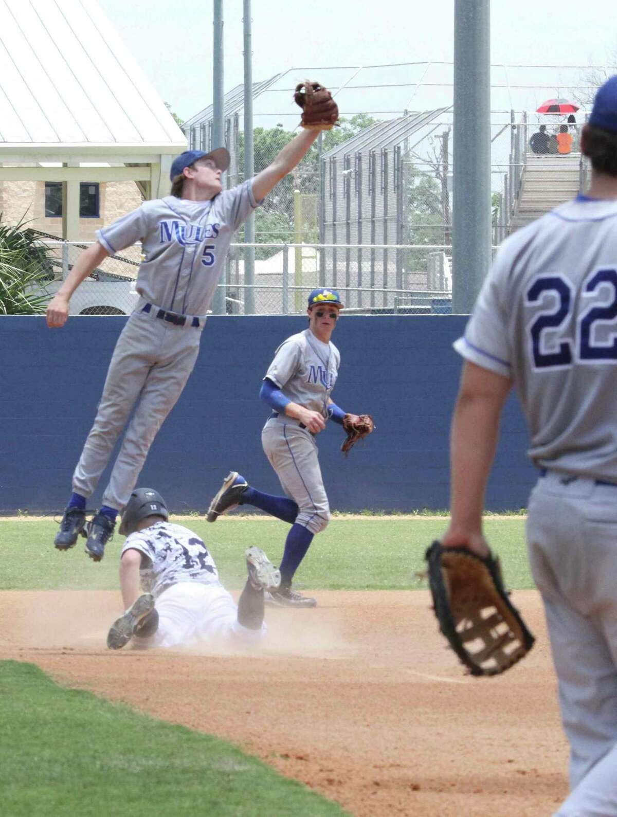 Alamo Heights junior Kalen Brockwell nearly snags the throw to keep Boerne Champion senior Trevor Harlos from advancing on base in a Class 4A third-round playoff game. The Chargers knocked out the Mules in two games, 12-1 Friday, and 10-2 Saturday.