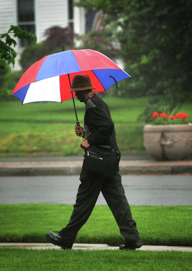 A man uses a big umbrella to stay dry as he walks in the rain on Main Street in Stratford on Monday, May 21, 2012. Photo: Brian A. Pounds / Connecticut Post