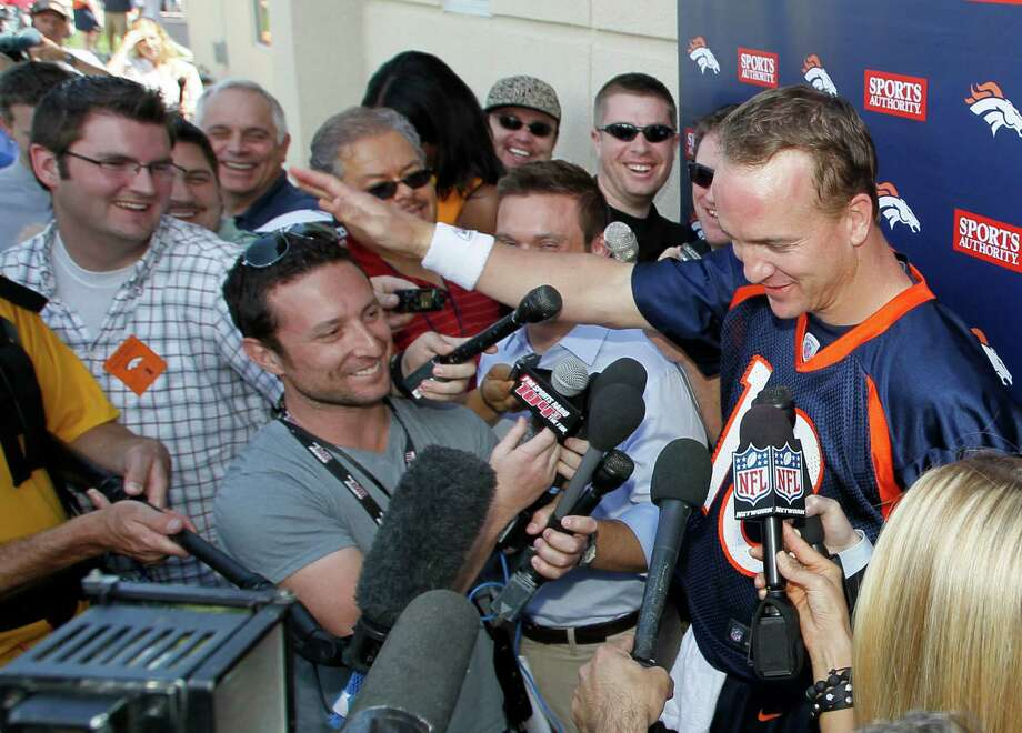 Denver Broncos quarterback Peyton Manning, right, reaches out to pat KKFM radio reporter Brandon Krisztal on the head after Manning made a joke about the reporter's stature while talking to the media after Manning's first mini camp since joining the team at Broncos headquarters in Englewood, Colo., on Monday, May 21, 2012. Photo: AP