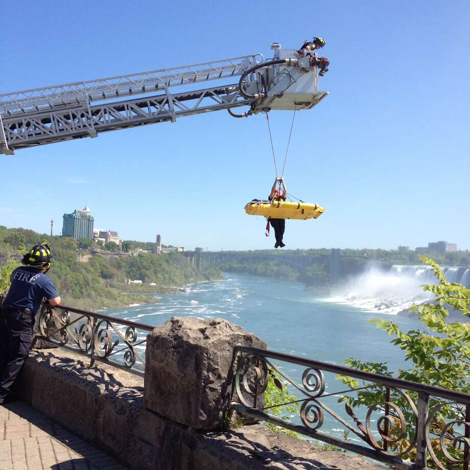 In this photo provided by Jared Fisk, Niagara Falls emergency officials rescue a man who plunged over Niagara Falls and survived in an apparent suicide attempt, Monday, May 21, 2012. The man is only the third person known to have gone over without a safety device and live. A waiting helicopter flew him to Hamilton General Hospital, where a spokeswoman says he has critical but non-life-threatening injuries. Photo: AP