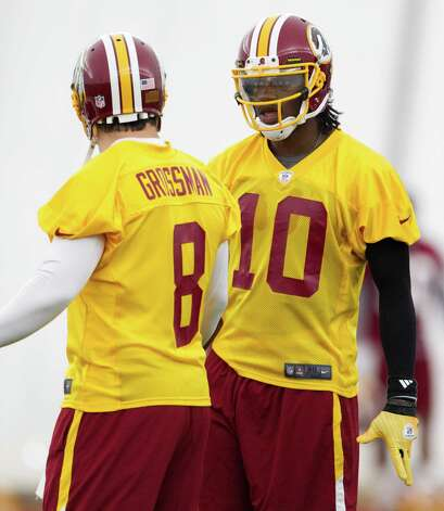 Washington Redskins rookie quarterback Robert Griffin III, right, talks with quarterback Rex Grossman during an organized team activity for the NFL football team on Monday, May 21, 2012 in Ashburn, Va. Photo: AP