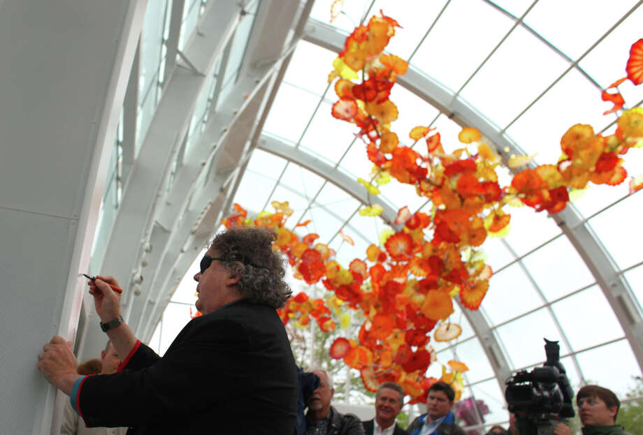 "Artist Dale Chihuly autographs a beam in the ""Glasshouse"" during the grand opening of the Dale Chihuly Garden and Glass museum at the Seattle Center on Monday, May 21, 2012. Photo: JOSHUA TRUJILLO / SEATTLEPI.COM"