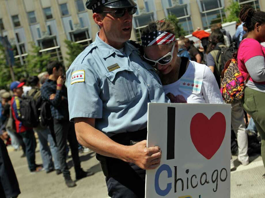 Protester Susann Doveikis-West hugs a Chicago Police Officer during a protest in front of President Barack Obama's campaign headquarters during NATO Summit in Chicago, Illinois, on Monday, May 21, 2012. Photo: Scott Strazzante, McClatchy-Tribune News Service / Chicago Tribune