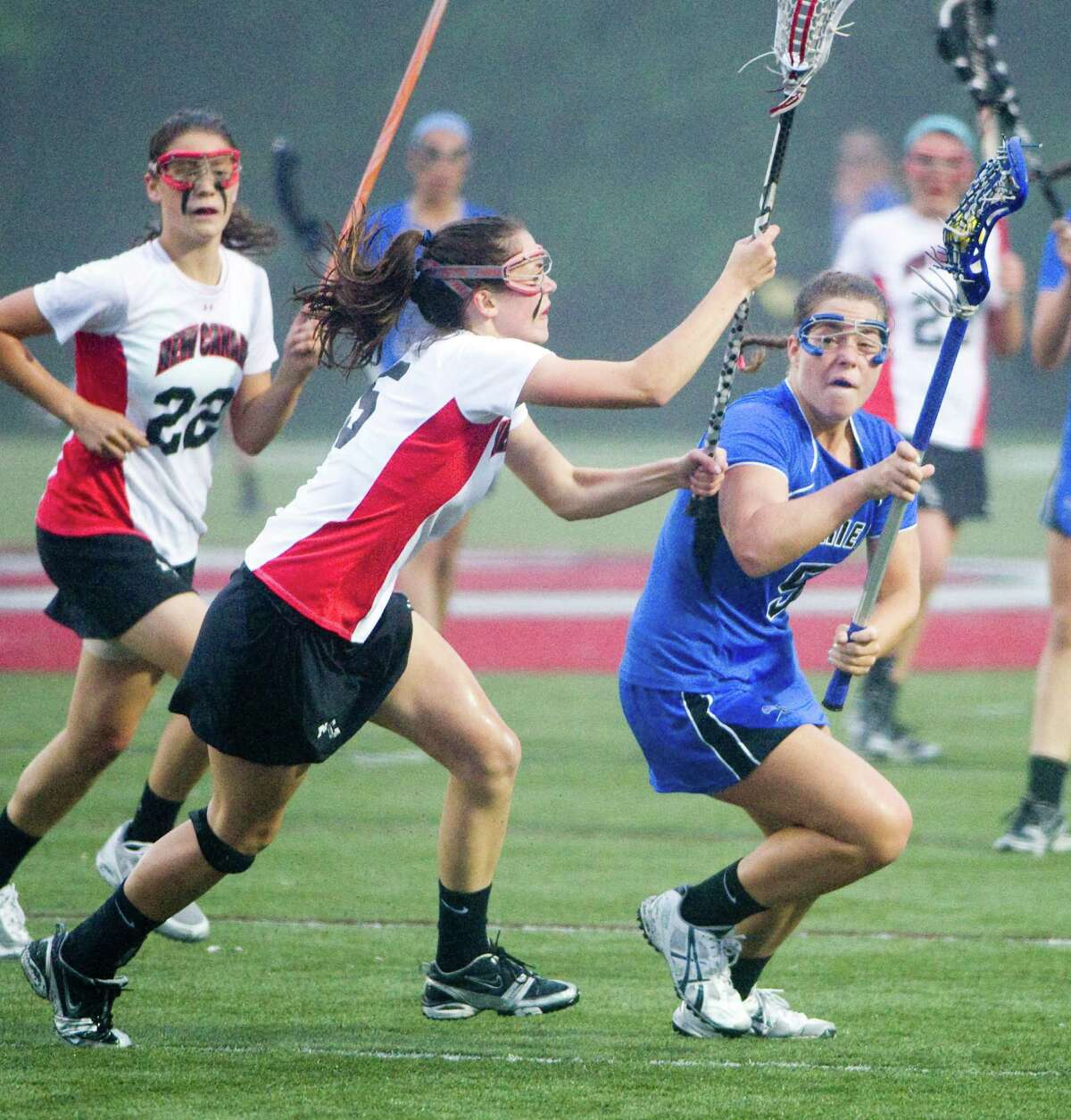 Darien's Brynn Gasparion turns the ball as New Canaan's Brianna McEwan closes in as New Canaan and Darien face off in the FCIAC Girls Lacrosse Semifinals at Dunning Field in New Canaan, Conn., May 21, 2012.