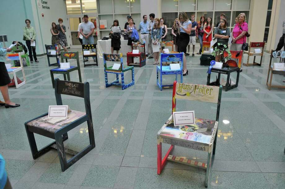 "Visitors view some of the 41 chairs from 24 Capital Region high schools during UAlbany's ""Chairs That Tell a Story,"" where high school students blended art and literature as they depict a literary classic on one of the university's original 1960's oak chairs, during an awards ceremony for the event, in the atrium of the Science Library at UAlbany on Monday May 21, 2012 in Albany, NY. The chairs will be available to view online, and will go back on display at the library on October 12 of this year.   (Philip Kamrass / Times Union ) Photo: Philip Kamrass / 00017754A"