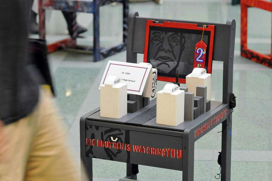 """A chair based on George Orwell's """"1984"""", by students from Greenwich High School, one of the 41 chairs from 24 Capital Region high schools on display during UAlbany's """"Chairs That Tell a Story,"""" where high school students blended art and literature as they depict a literary classic on one of the university's original 1960's oak chairs, during an awards ceremony for the event, in the atrium of the Science Library at UAlbany on Monday May 21, 2012 in Albany, NY. The chairs will be available to view online, and will go back on display at the library on October 12 of this year.   (Philip Kamrass / Times Union ) Photo: Philip Kamrass / 00017754A"""