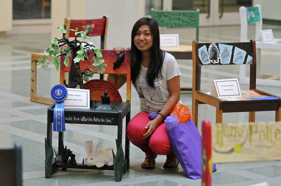 "Rensselaer High School junior Paw Law Eh Zan won a first place ribbon for her chair based on John Steinbeck's ""Of Mice and Men,"" one of the 41 chairs from 24 Capital Region high schools on display during UAlbany's ""Chairs That Tell a Story,"" where high school students blended art and literature as they depict a literary classic on one of the university's original 1960's oak chairs, during an awards ceremony for the event, in the atrium of the Science Library at UAlbany on Monday May 21, 2012 in Albany, NY. The chairs will be available to view online, and will go back on display at the library on October 12 of this year.   (Philip Kamrass / Times Union ) Photo: Philip Kamrass"