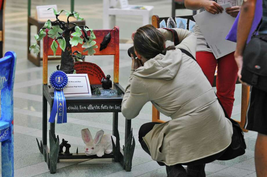 "Van Rensselaer Elementary School art teacher Tessa Sedlar photographs Rensselaer High School junior Paw Law Eh Zan' chair based on John Steinbeck's ""Of Mice and Men,"" left, one of the 41 chairs from 24 Capital Region high schools on display during UAlbany's ""Chairs That Tell a Story,"" where high school students blended art and literature as they depict a literary classic on one of the university's original 1960's oak chairs, during an awards ceremony for the event, in the atrium of the Science Library at UAlbany on Monday May 21, 2012 in Albany, NY. The chairs will be available to view online, and will go back on display at the library on October 12 of this year.   (Philip Kamrass / Times Union ) Photo: Philip Kamrass / 00017754A"