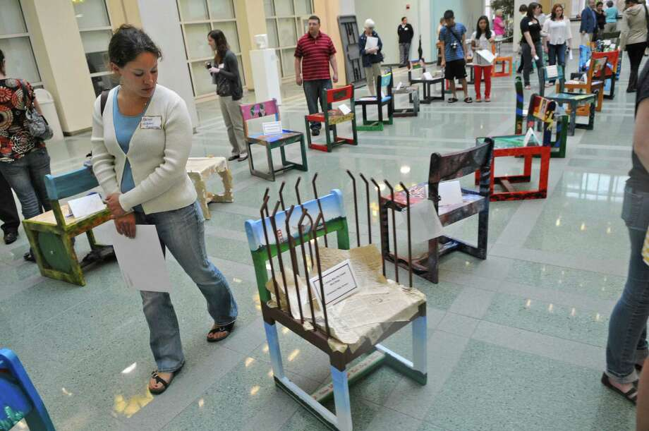 "Martha Houghton, Chairman of the Art Department at the Albany Academies, walks past a chair based on Maya Angelou's ""I Know Why the Caged Bird Sings,"" by Schalmont High School junior Breena Sperry, one of the 41 chairs from 24 Capital Region high schools on display during UAlbany's ""Chairs That Tell a Story,"" where high school students blended art and literature as they depict a literary classic on one of the university's original 1960's oak chairs, during an awards ceremony for the event, in the atrium of the Science Library at UAlbany on Monday May 21, 2012 in Albany, NY. The chairs will be available to view online, and will go back on display at the library on October 12 of this year.   (Philip Kamrass / Times Union ) Photo: Philip Kamrass / 00017754A"
