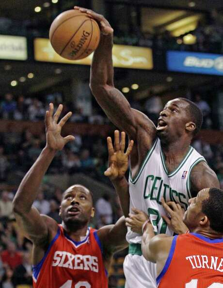 Boston Celtics' Brandon Bass, center, reaches for a rebound against Philadelphia 76ers defenders Elton Brand, left, and Evan Turner during the first quarter of Game 5 in their NBA basketball Eastern Conference semifinal playoff series in Boston, Monday, May 21, 2012. Photo: AP