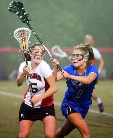 New Canaan's Brianna McEwan meets resistance from Darien's Emily Tropsa as New Canaan and Darien face off in the FCIAC Girls Lacrosse Semifinals at Dunning Field in New Canaan, Conn., May 21, 2012. Photo: Keelin Daly / Stamford Advocate