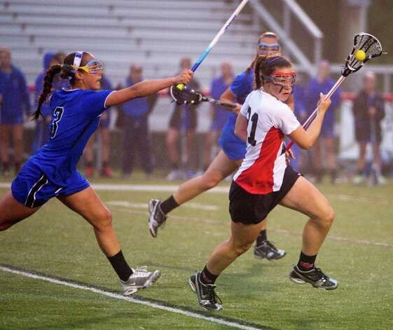 Darien's Dillon Schoen closes in on New Canaan's Abigail Sawabini as New Canaan and Darien face off in the FCIAC Girls Lacrosse Semifinals at Dunning Field in New Canaan, Conn., May 21, 2012. Photo: Keelin Daly / Stamford Advocate