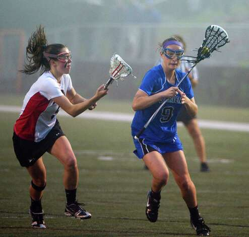 Darien's Emily Stein looks to move the ball past New Canaan's Brianna McEwan as  New Canaan and Darien face off in the FCIAC Girls Lacrosse Semifinals at Dunning Field in New Canaan, Conn., May 21, 2012. Photo: Keelin Daly / Stamford Advocate