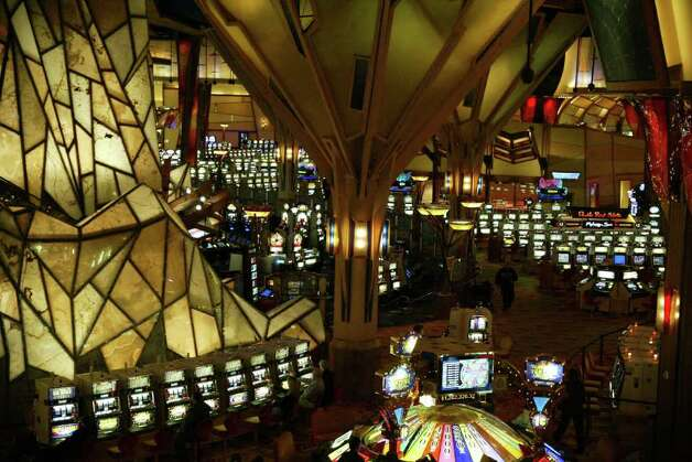 A few visitors walk along the Mohegan Sun Casino slot machines, Thursday, Nov. 19, 2009. Photo: Phil Noel / Connecticut Post