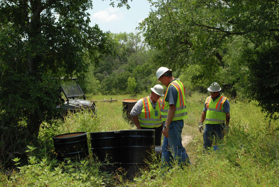 SAWS employees Andrew Wiatrek (center) and Juan Garza, examine unmarked 55-gallon drums that were left in Leon Creek near West Huebner Road on Monday, May 21, 2012.  The drums, which had no identifying stickers, appeared to be filled with a solid material. Photo: Colin McDonald, San Antonio Express-News / © 2012 San Antonio Express-News