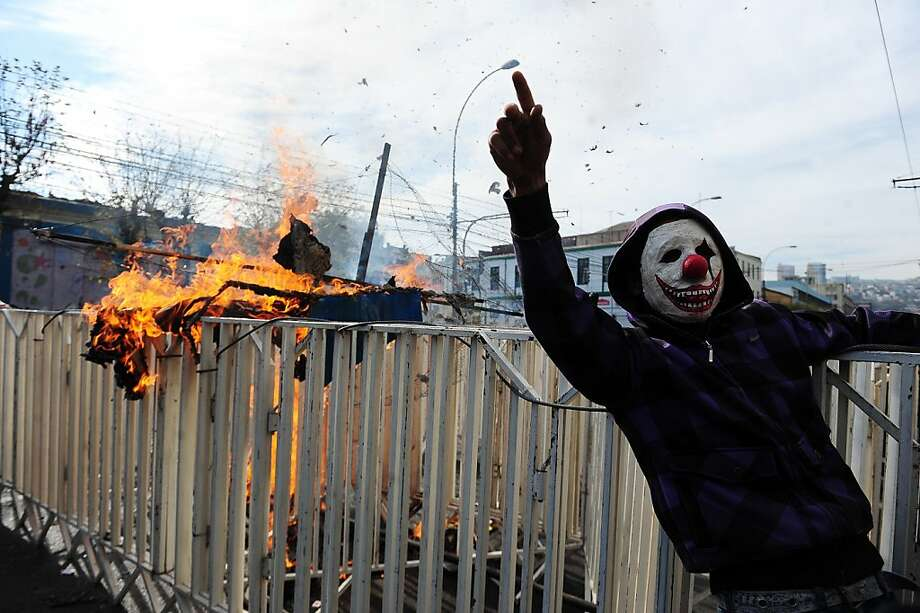 Demonstrators chant slogans during clashes with riot police in the surroundings of the Congress in Valparaiso, Chile, as President Sebastian Pinera delivers his annual message to the nation on May 21, 2012.     TOPSHOTS/AFP PHOTO/CLAUDIO SANTANACLAUDIO SANTANA/AFP/GettyImages Photo: Claudio Santana, AFP/Getty Images