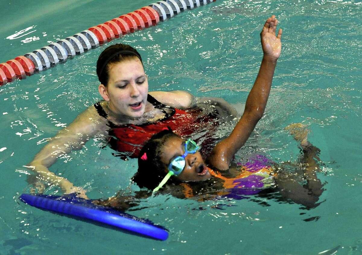 Swim instructor Jordan Stewart works with Jamauree Reynoso, 7, of Danbury, in a Guppy level swim program at the Boughton Street Y in Danbury Monday May 21, 2012.