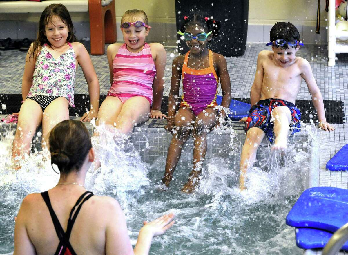 Young swimmers learn to kick in a Guppy level swim program at the Boughton Street Y in Danbury Monday May 21, 2012. At each end are Samantha Kivel, 8, and her brother Dylan, 6, of Redding, Devin Donaty, 6, left center, and Jamauree Reynoso, 7, both of Danbury.