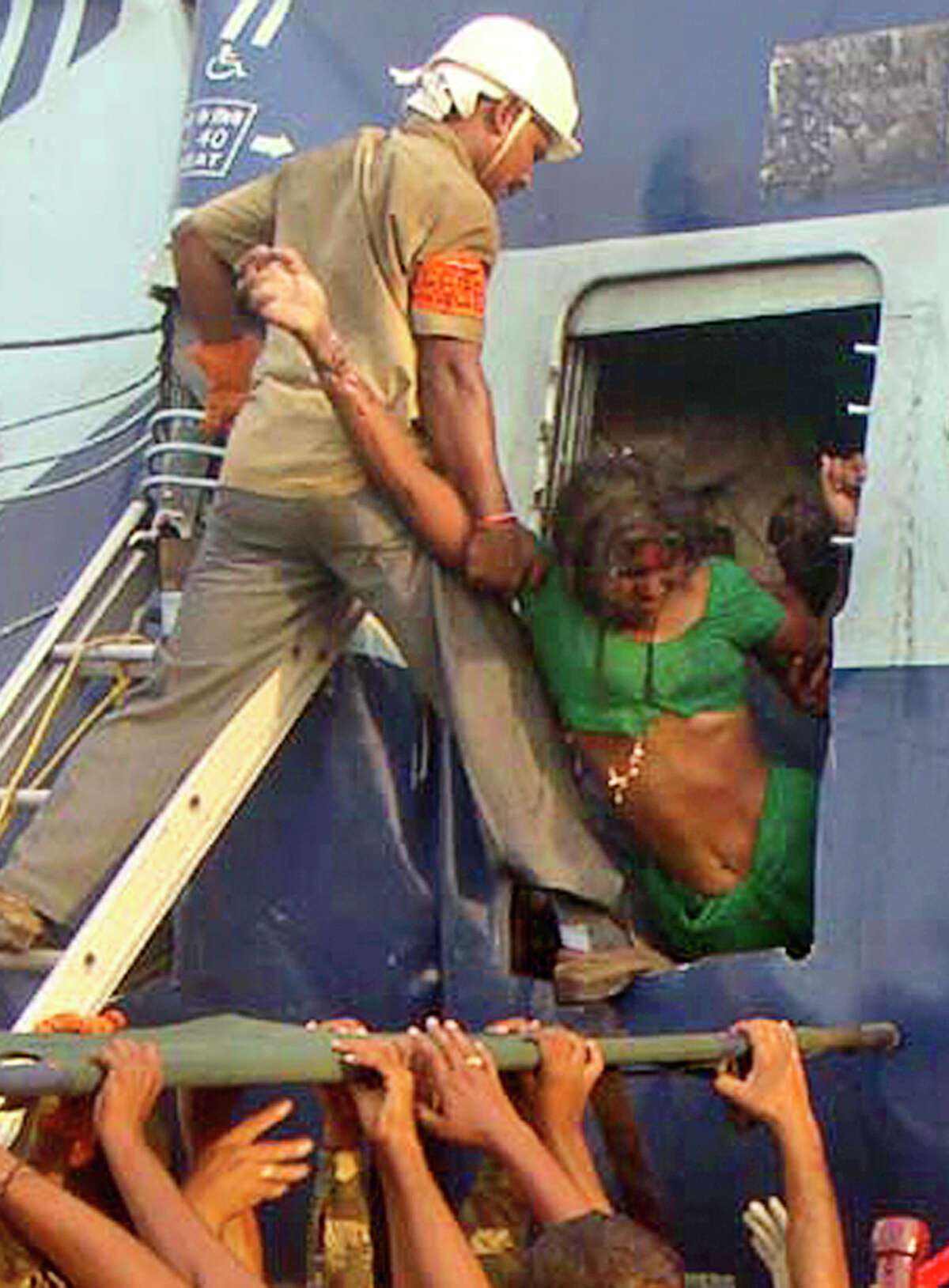 ALTERNATE CROP OF DEL114 - Rescuers evacuate an injured woman from the site of a train accident at a station near Penukonda, about 170 kilometers (105 miles) north of Bangalore, India, Tuesday, May 22, 2012. The passenger train rammed into a parked freight train and burst into flames before dawn Tuesday, killing more than a dozen people in southern India, officials said.