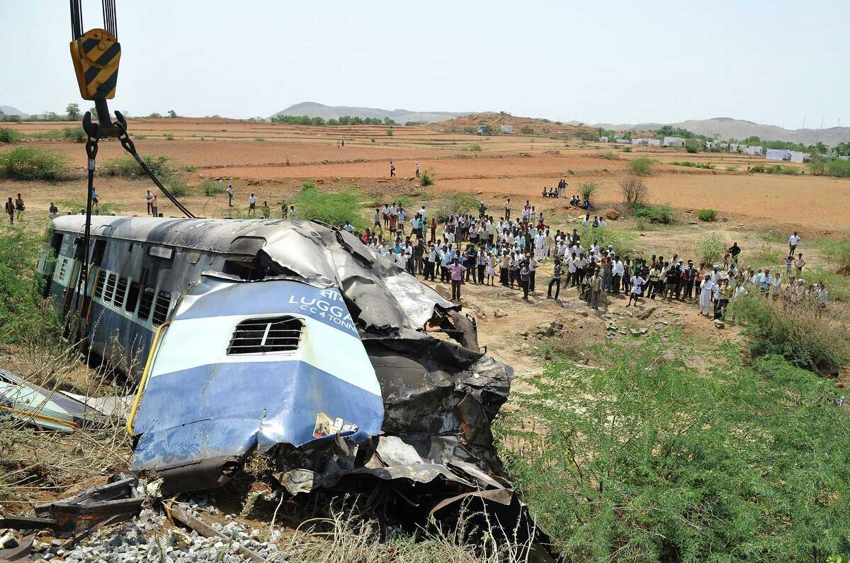 Local villagers watch as a heavy duty railway crane lifts the mangled remains of a coach of the Bangalore-bound Hampi Express after it collided with a stationary goods train near Penneconda town in Ananthpur District, about 145 kms from Bangalore on May 22, 2012. At least 19 people were killed and 36 injured when a passenger train slammed into a stationary goods train in southern India, a local railway official told AFP. AFP PHOTO/Manjunath KIRANManjunath Kiran/AFP/GettyImages
