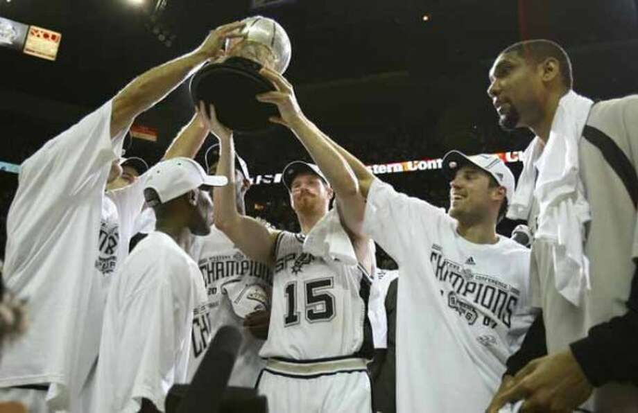 Spurs' Matt Bonner (15) with help from Beno Udrih, right and other teammates hoist the Western Conference Championship trophy after defeating the Utah Jazz in the Western Conference Finals game five in San Antonio Wednesday May 30, 2007.  (DOUG SEHRES/STAFF) (SAN ANTONIO EXPRESS-NEWS)