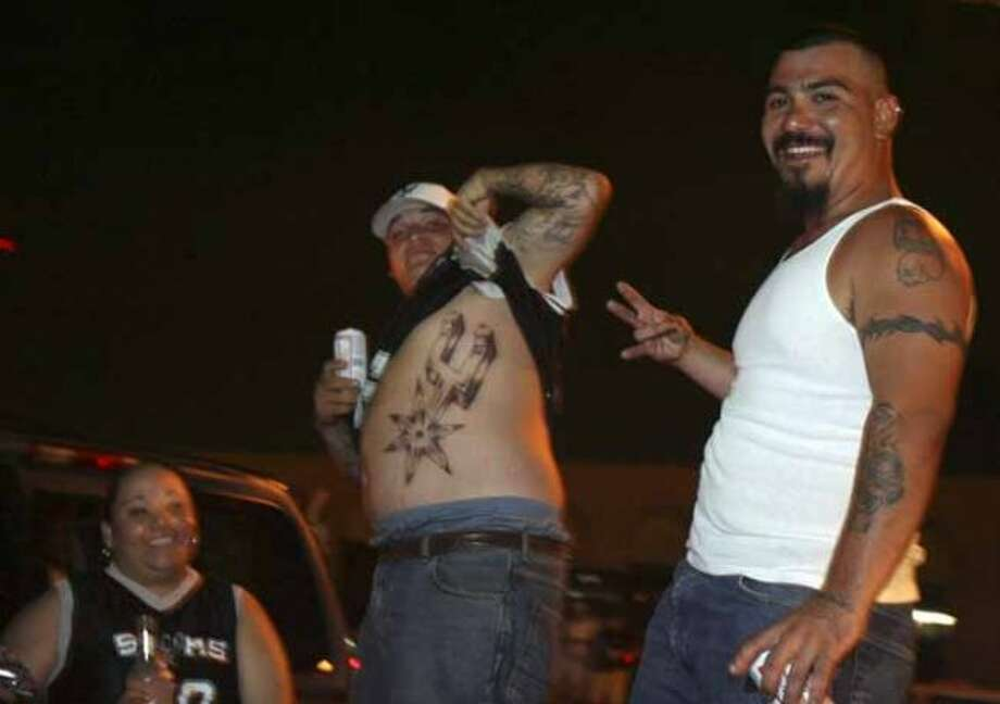METRO --  Richard Hernandez shows off the tattoo he got Wednesday.  His wife Lilly Hernandez (left) said that Richard had that much faith that the Spurs would win Thursday.  Friend John Perez join in celebrating the Spurs' fourth NBA championship win Dolorosa at Market Square Thursday June14, 2007.  (Robert McLeroy/San Antonio Express-News) (San Antonio Express-News)