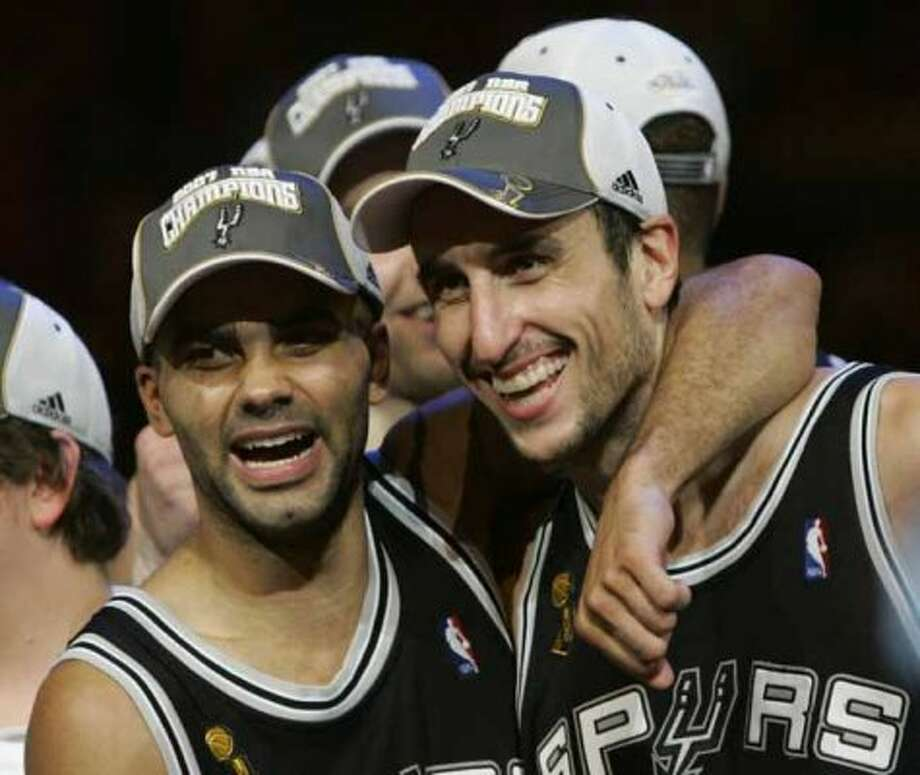 San Antonio Spurs' Tony Parker, left, from France,  hugs Manu Ginobili from Argentina, after the Spurs beat the Cleveland Cavaliers, 83-82, in Game 4 to win the NBA basketball championship Thursday, June 14, 2007, in Cleveland. (AP Photo/Tony Dejak) (AP)