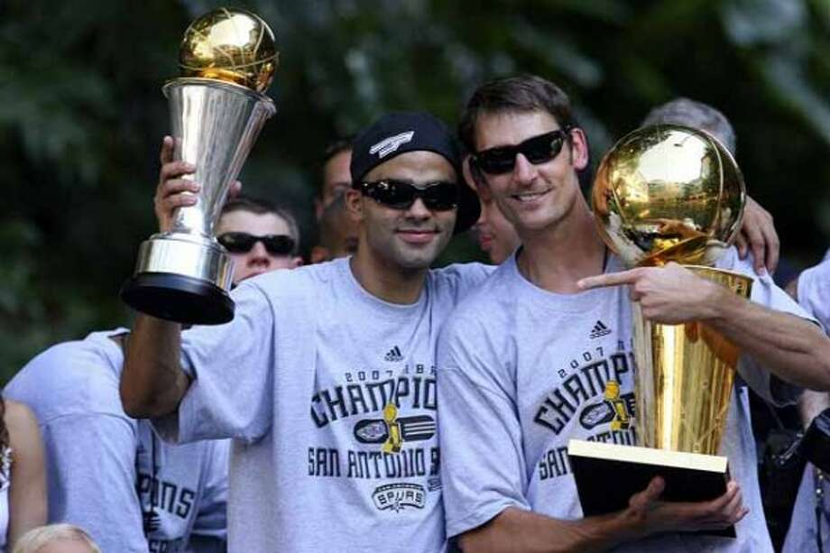 FOR METRO - Spurs' guard Tony Parker, of France, (09) holds the MVP throphy while  guard Brent Barry (17) holds one of the four championship trophies during the victory parade Sunday June 17, 2007, at the River Center Lagoon (EDWARD A. ORNELAS/STAFF) (SAN ANTONIO EXPRESS-NEWS)