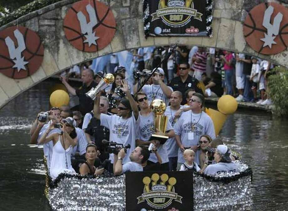 San Antonio Spurs Tony Parker, center left, and Brent Barry, center right, greet the crowd during a parade down the Riverwalk at the Arneson Theater in celebration of their fourth NBA Championship title on Sunday, June, 17, 2007.  ( JERRY LARA STAFF ) (SAN ANTONIO EXPRESS-NEWS)