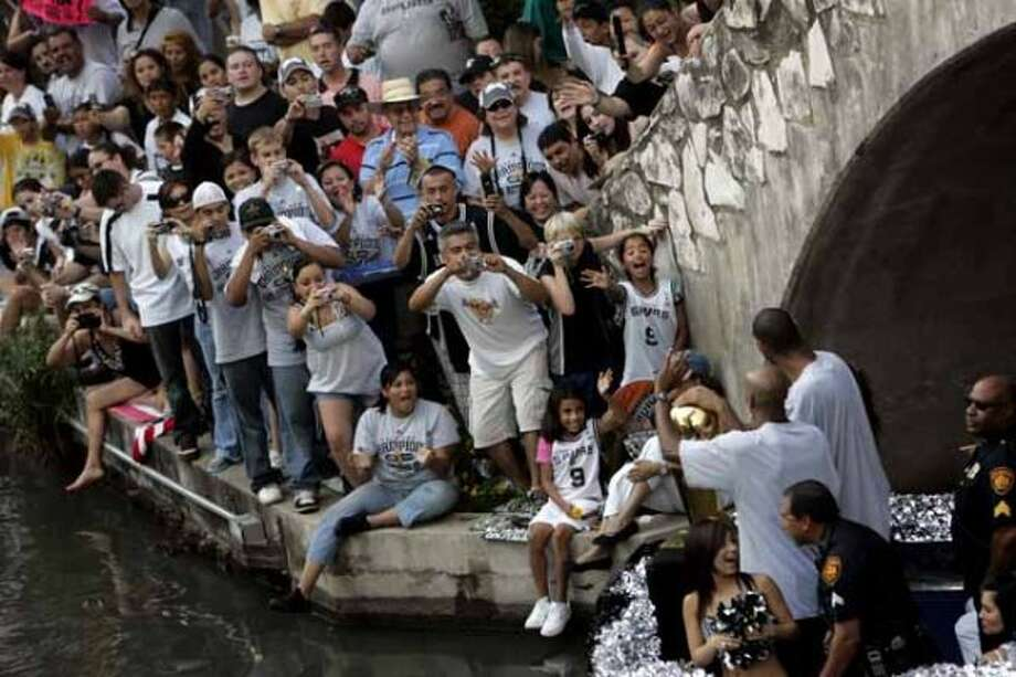 METRO - Fans cheer as Bruce Bowen, left, and Tim Duncan, right, round the bend near the Commerce Street bridge during the Spurs NBA Championship river parade on Sunday, June 17, 2007. Lisa Krantz/STAFF (SAN ANTONIO EXPRESS-NEWS)