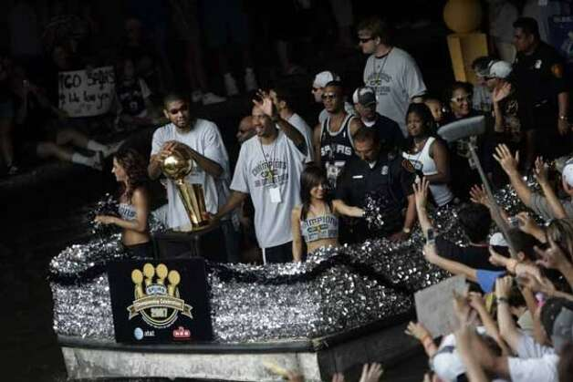 METRO - Tim Duncan, left, and Bruce Bowen, right, ride by fans near the Commerce Street bridge during the Spurs NBA Championship river parade on Sunday, June 17, 2007. Lisa Krantz/STAFF (SAN ANTONIO EXPRESS-NEWS)