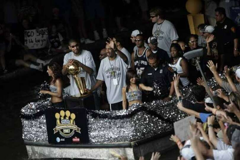 METRO - Tim Duncan, left, and Bruce Bowen, right, ride by fans near the Commerce Street bridge durin