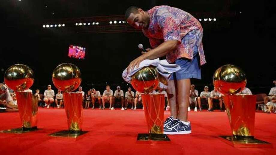 FOR METRO - Spurs' forward Robert Horry (5) polishes the championship trophies during the victory celebration held at the Alamodome Sunday June 17, 200. (EDWARD A. ORNELAS/STAFF) (SAN ANTONIO EXPRESS-NEWS)