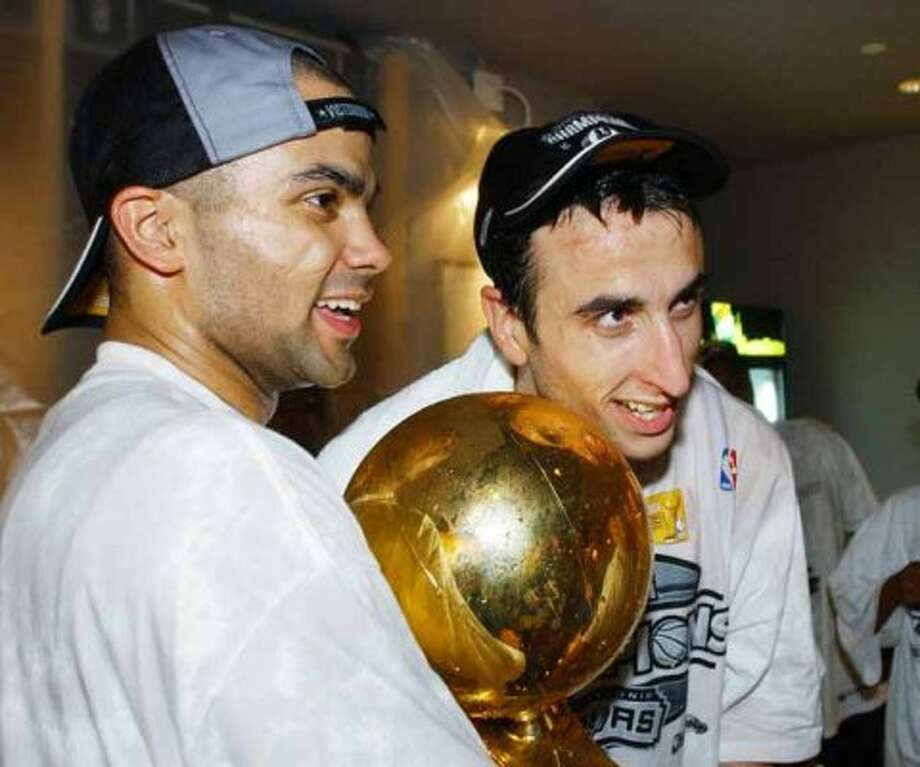 San Antonio Spurs players Tony Parker, left, and Emanuel Ginobili, right, hold the NBA Championship trophy after the Spurs defeated the New Jersey Nets 88-77 in Game 6 of the NBA Finals in San Antonio, Sunday, June 15, 2003. (AP Photo/Eric Gay) (AP)