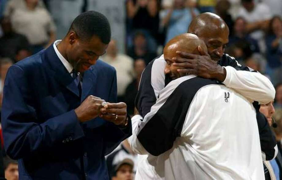 SPORTS   ---   Former Spur David Robinson looks Tuesday Night Oct. 28, 2003 in the SBC Center at his new NBA championship ring while Spurs Kevin Willis and Bruce Bowen celebrate getting their rings.        (WILLIAM LUTHER/STAFF) (SAN ANTONIO EXPRESS-NEWS)