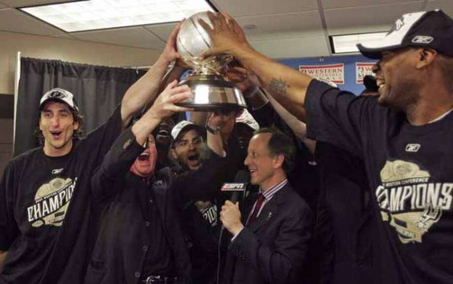 Spurs majority owner Peter Holt, second from left holds up the Western Conference championship trphy with help from Manu Ginobili, left, Tony Parker, center and Tony Massenburg. WILIAM LUTHER