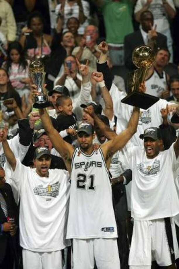 Spurs Tony Parker, left, Tim Duncan with both trophys and Bruce Bowen celebrate their NBA Championship during trophy presentation game 7 NBA Finals at the SBC Center in San Antonio Thursday June 23, 2005 . BAHRAM MARK SOBHANI/STAFF (SAN ANTONIO EXPRESS NEWS)